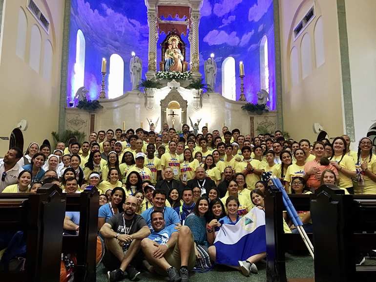 Miami's 135 World Youth Day pilgrims pose for a photo at the Santuario Nacional Corazon de Maria after celebrating Mass with Florida's bishops before embarking on the 10-mile trek to the site of the overnight vigil and final Sunday Mass with Pope Francis.