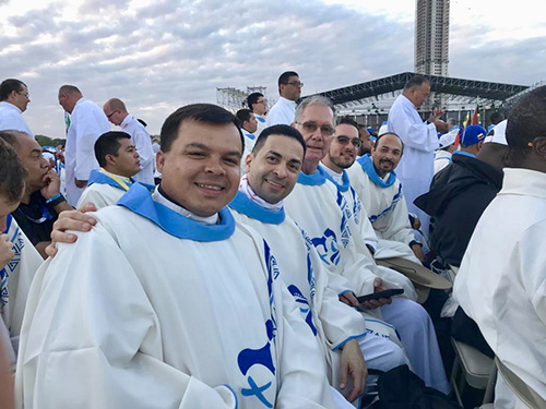 Archdiocesan priests pose for a photo before concelebrating the final Mass of World Youth Day in Panama with Pope Francis. From left: Father Elvis Gonzalez, vocations director; Father Jose Alfaro, pastor of Blessed Trinity, Miami Springs; Father James McCreanor, retired pastor of Sacred Heart in Homestead; Father Bryan Garcia, administrator of St. Bernadette in Hollywood; and Jesuit Father Christian Saenz, who accompanied a group of students from Belen Jesuit Prep in Miami.