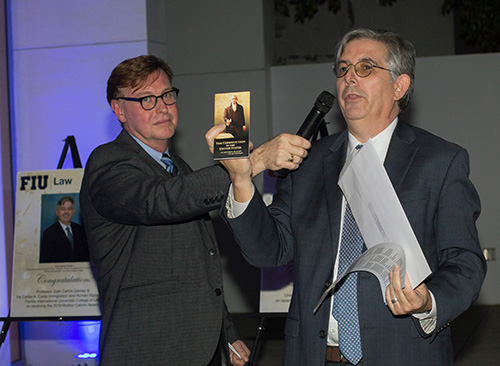 Randolph McGrorty, CEO of Catholic Legal Services, holds the microphone for Mother Cabrini Award recipient Juan Carlos Gomez of Florida International University, who held up a copy of the U.S. Constitution during his acceptance speech.