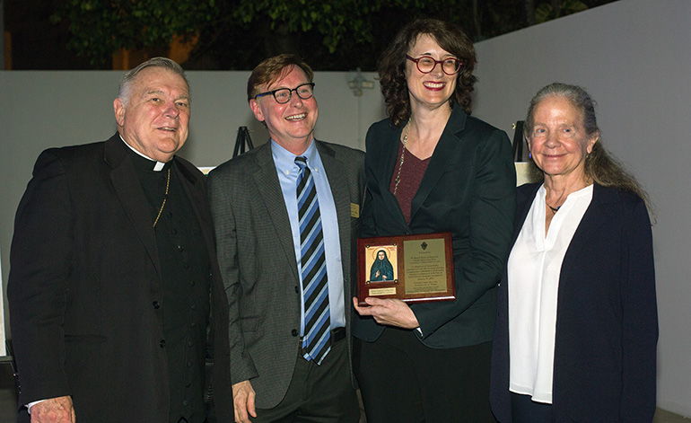 From left: Archbishop Thomas Wenski and Randolph McGrorty, CEO of Catholic Legal Services, pose with Mother Cabrini award recipient Rebecca Sharpless, professor of Clinical Legal Education at the University of Miami and director of UM's Immigration Clinic, and Patricia White, dean of UM's law school.