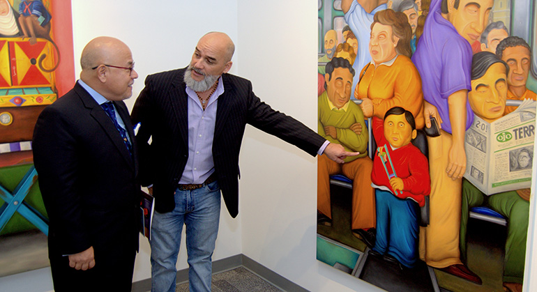 "Hugo Orezzoli, right, shows his painting ""The Bus"" to David Hurtado Fudinaga, Miami-based deputy general consul of Peru, during the opening of Orezzoli's art show at St. Thomas University."