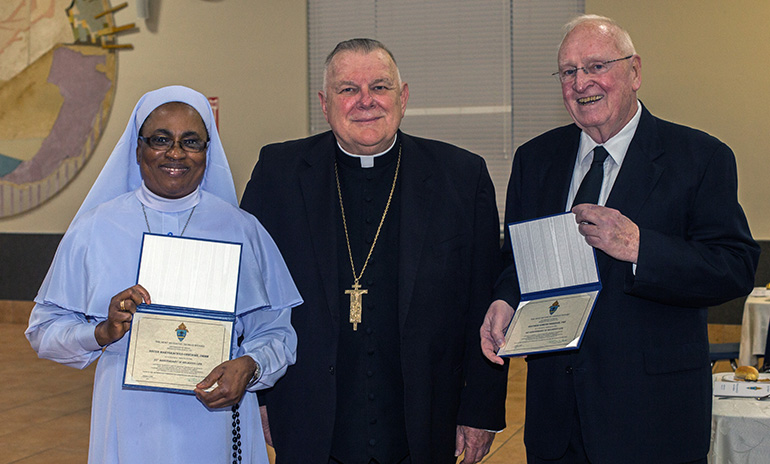 Sister Marygracious Onwukwe, of the Daughters of Mary, Mother of Mery, and Marist Brother Edmund Sheehan, pose with Archbishop Thomas Wenski and the certificates they received marking their 25th and 60th jubilees, respectively.
