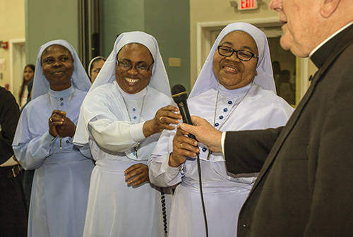 Sister Marygracious Onwukwe hands the microphone to Archbishop Thomas Wenski after she and Sisters Therese Martin and Sister Mary Agatha, of the Daughters of Mary, Mother of Mercy, sang a Nigerian food blessing at the reception that followed the Mass for the World Day of Consecrated Life.