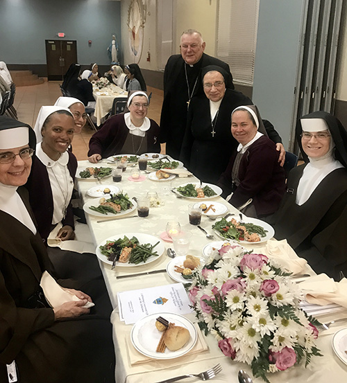 Archbishop Thomas Wenski poses with members of two religious communities, the Servants of the Pierced Hearts of Jesus and Mary and the Carmelites of the Most Sacred Heart of Los Angeles, at the dinner that followed the annual Mass for the World Day of Consecrated Life, Feb. 2 at St. Mary Cathedral.