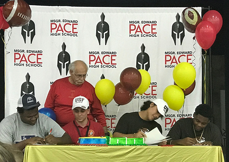 Four Msgr. Edward Pace High School football players signed letters of intent Feb. 6 to play at the college level. From left: Bryner Joseph signed with St. Thomas University, Miami Gardens; Tyler Carmona, Thomas Willis and Rayvaugh Choute all signed with the University of St. Francis, Illinois. Standing behind them is Pace Athletic Director Joe Zaccheo.