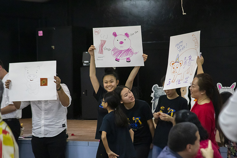 Kids participate in a game during the reception that followed the Chinese New Year Mass. The game consisted of drawing pictures of a pig, the Chinese Zodiac animal for this lunar year.