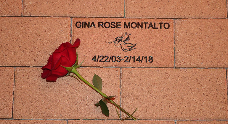 A red rose is placed on a brick near the Mary Help of Christians Church entrance in Parkland, bearing the name of Gina Rose Montalto. Gina, 14, whose family are parishioners, was killed in the shooting at Marjory Stoneman Douglas High School.