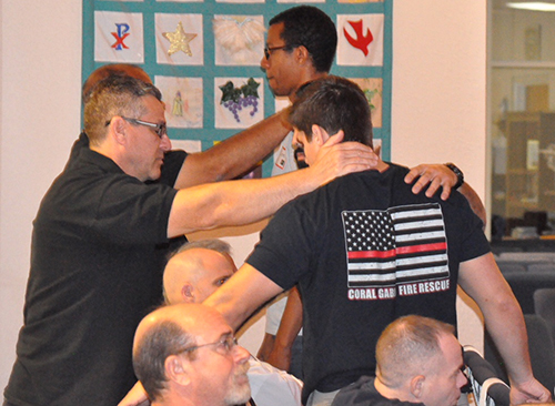 Men pray for each other during one of the ManUp conferences held at St. Edward Church in Pembroke Pines.