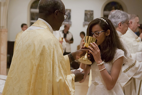 Jennifer Ortiz, then 12, celebrates her first Communion during the Easter Vigil Mass at St. Mary Cathedral back in 2016. Members of St. Anthony Parish's Women's Guild are now praying individually for each of the 26 children in the religious education program who will make their first Communion March 2.