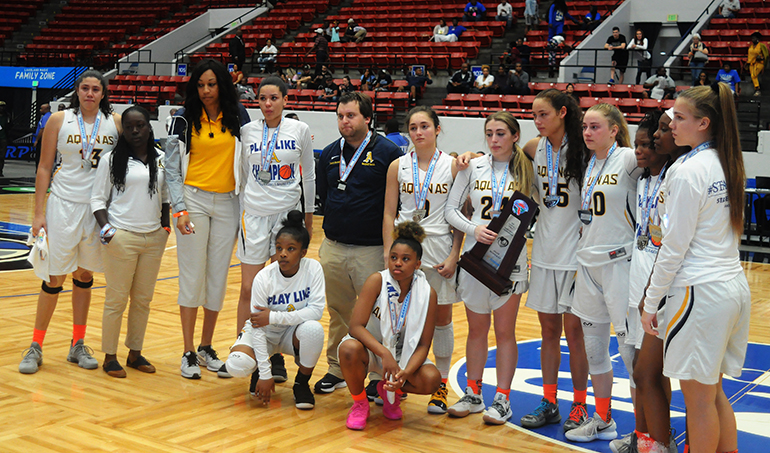 St. Thomas Aquinas coach Oliver Berens and his team pose with the state runner-up trophy after the Raiders lost 58-52 in overtime to Tampa Bay Tech on Saturday, March 2, in the FHSAA Class 8A state girls basketball championship game at the RP Funding Center in Lakeland.