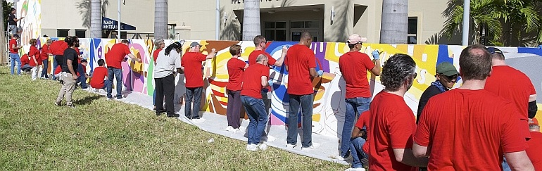 Workers paint a 100-foot mural at Camillus House in Miami. Wearing red shirts are workers from the Dow Chemical Company, with black shirts on Camillus House staffers.