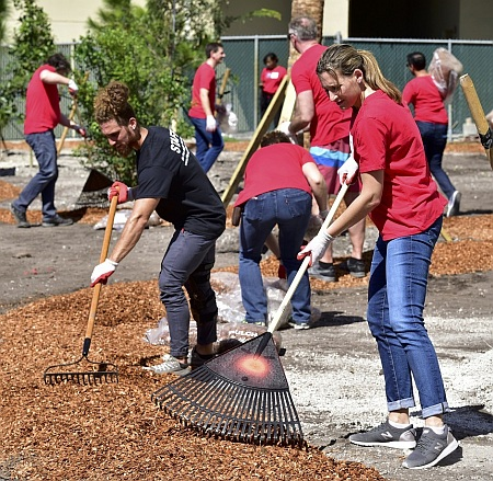 Workers spread mulch for a walking path at Camillus House in Miami. Wearing red shirts are workers from the Dow Chemical Company, with black shirts on Camillus House staffers.