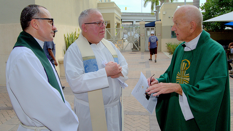 Hospitaller Brother Raphael Mieszala, right, chats with two concelebrants before his farewell Mass at Camillus House.  From left are Father Matias Hualpa of St. John Vianney College Seminary and Father Gabriel Vigués of St. Francis de Sales Church, Miami Beach.