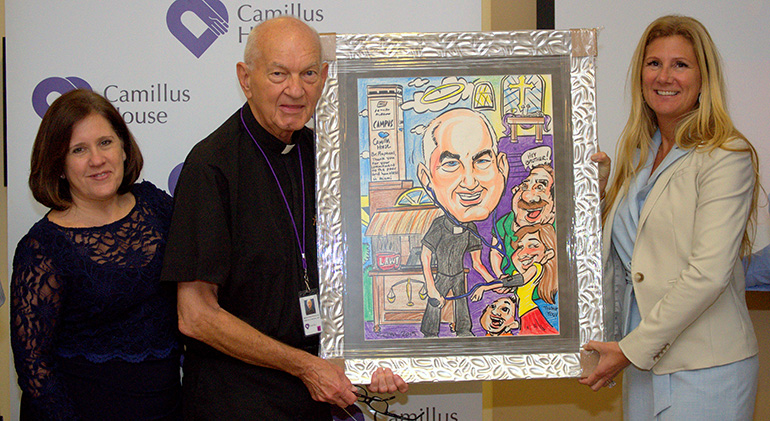 Officers of Camillus House present Hospitaller Brother Raphael Mieszala with an affectionate caricature after his farewell Mass at the shelter for the homeless. With him are CEO Hilda Fernandez, left, and Andria Hanley, vice president of development.
