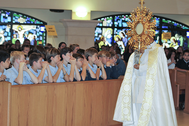 Father Elvis Gonzalez, director of vocations for the Archdiocese of Miami, processes with the Blessed Sacrament at the conclusion of the Focus 11 vocations rally Feb. 27 at host St. Gregory Parish in Plantation.
