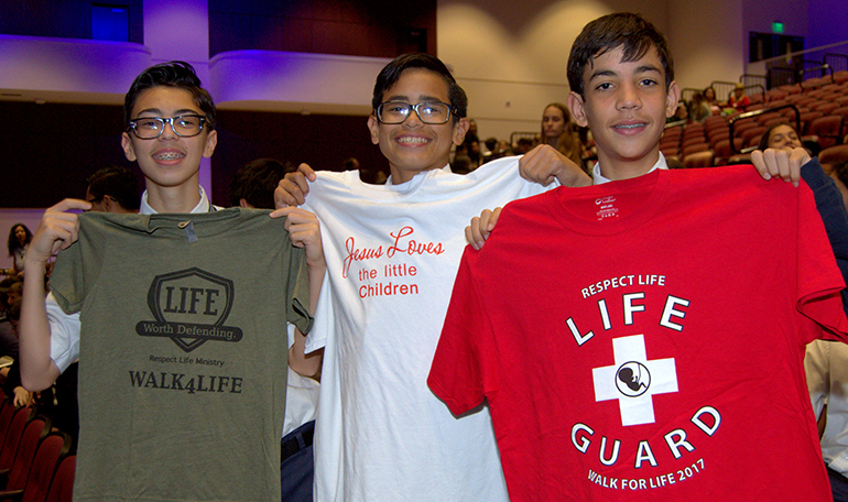 Eighth graders from Immaculate Conception School show the T-shirts they got during Chastity Day rally, held in Pembroke Pines. From left are Anthony Torres, Jose Arauz and Christopher Victores.