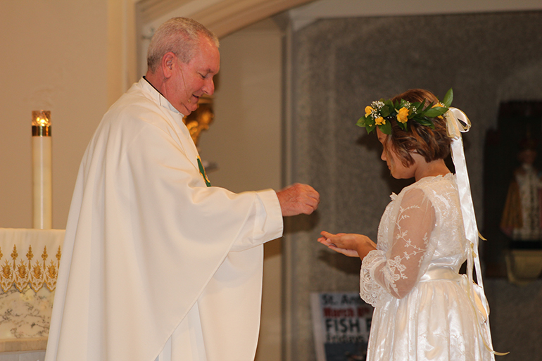 Father Michel Grady, pastor of St. Anthony Parish in Fort Lauderdale, distributes the Eucharist to Sophia Oberhelman, 10.