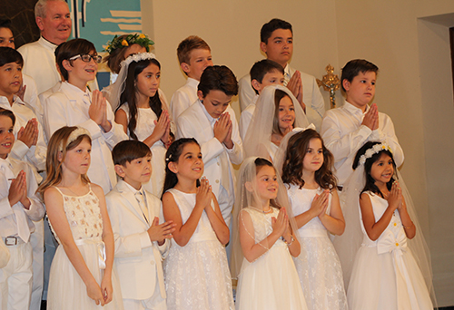 Father Michael Grady, pastor of St. Anthony Parish, gathers with children after they received their first Communion May 2 at the Fort Lauderdale church.