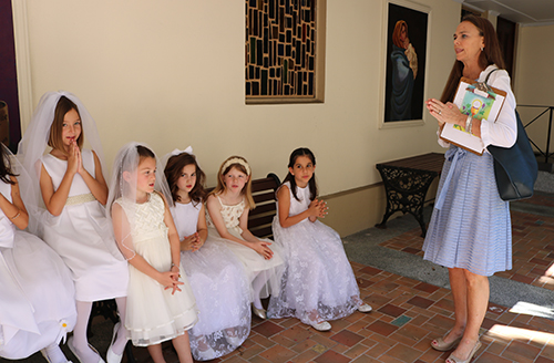 St. Anthony catechist Dot Bevins talks to young girls moments before the start of the Mass where they received their first Communion.