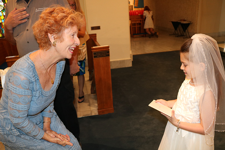 Dolores McDiarmid of St. Anthony Parish greets Delaney Lefka, the first communicant who had been at the center of her prayers over the past months.