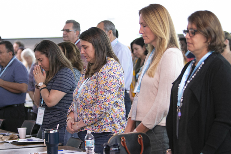 Participants pray at the start of the keynote talk by Sister Miriam James Heidland of the Sisters of Our Lady of the Most Holy Trinity, during the archdiocesan Evangelization Summit, March 16, 2019, at Msgr. Edward Pace High School in Miami Gardens.