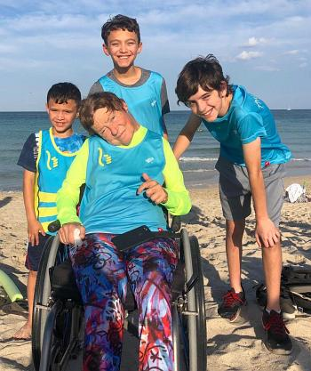 Youths take part in the April 14 South Beach Triathlon along with disabled athlete Kerry Gruson, center. The boys, from left, are Anthony and Lewis Perez, students at St. Mark School; and their friend Esteban Bird, a student at Mater Grove Academy in Miami.