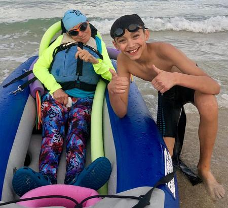 Lewis Perez, a sixth-grader at St. Mark School, gives a thumbs-up at the April 14 South Beach Triathlon. He teamed up for the event with disabled athlete Kerry Gruson, left, of ThumbsUp International.