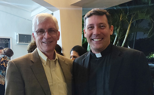 Ralph Martin, center, poses with his former student, Father Richard Vigoa, temporary administrator of St. Augustine Church and Catholic Student Center in Coral Gables, after giving a talk about the
