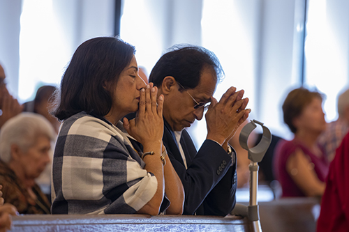 Mary and George Vells, parents of pastor Father Biju Vells, pray during the Mass celebrated by Archbishop Thomas Wenski in commemoration of the 60th anniversary of St. Pius X Church in Fort Lauderdale.