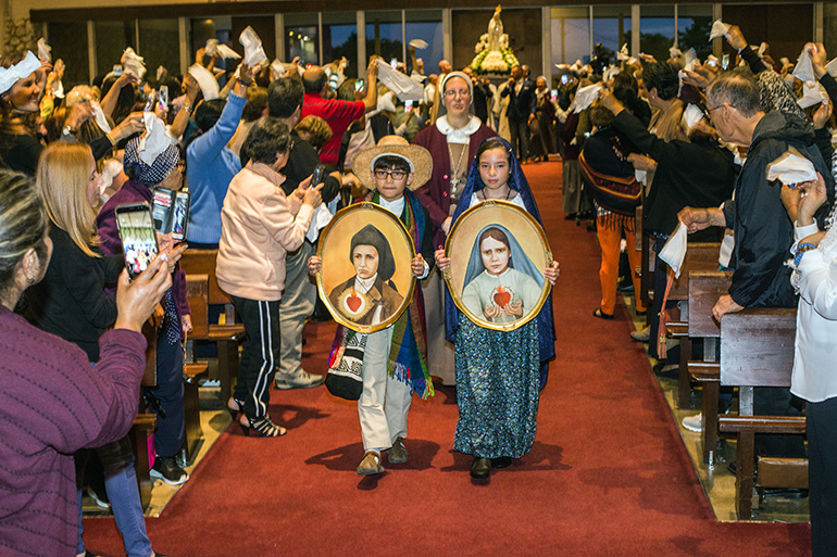 Luciano Garzon, 10, and Mariana Canedo, 10, dressed as the shepherd children St. Francisco and St. Jacinta, enter St. Michael Church followed by Sister Grace Heinrich of the Servants of the Pierced Hearts of Jesus and Mary.
