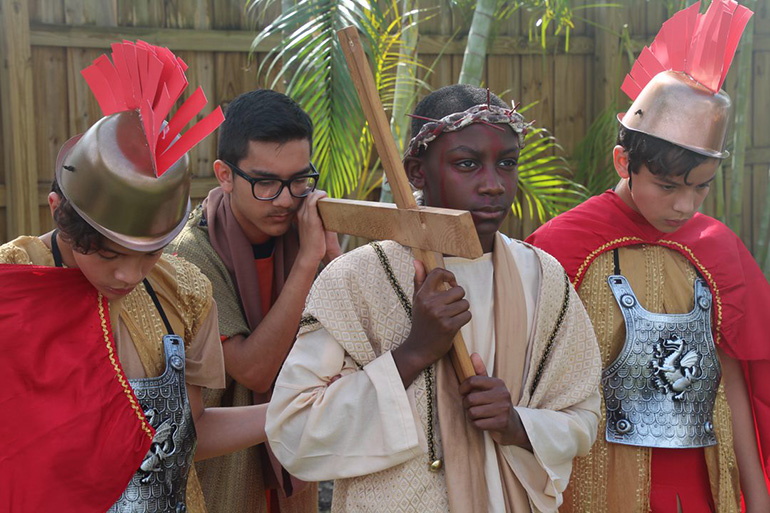 Mother of Our Redeemer eighth-graders re-enact Jesus carrying his cross. From left: Nicholas Lozano, Ricardo Machado, Simeon Fleuridor, and Jonathan Lozano.