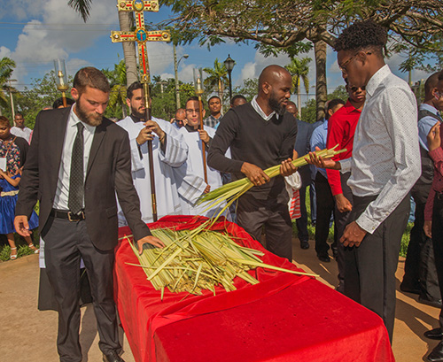 Mass-goers pick up the blessed palms at the start of Palm Sunday Mass, April 14, 2019.