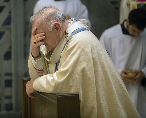 Archbishop Thomas Wenski prays before the Blessed Sacrament at the conclusion of Holy Thursday Mass at St. Mary Cathedral.