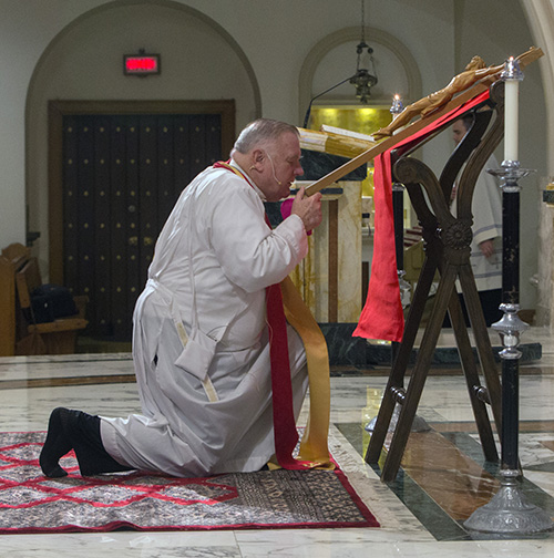 Archbishop Thomas Wenski venerates the Cross during the Good Friday service at St. Mary Cathedral.
