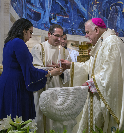 Archbishop Thomas Wenski hands catechumen Nathalie Matos a candle symbolizing her moving from death to life in Christ through baptism.