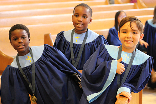 Dressed in the choir robes, Christian Celian, Dylhann Pierre, and Nicholas Cortes from St. Luke's Church choir in Palm Springs, a part of the Diocese of Palm Beach, pose for a photo before the start of Mass at the American Federation Pueri Cantores Festival at St. Bonaventure Church, Davie.