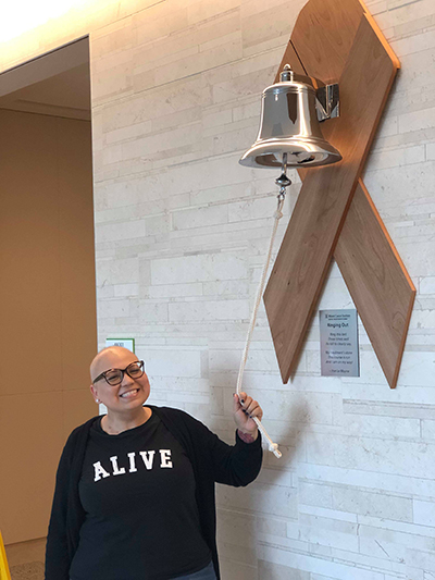 Angela Suazo rings the treatment completion victory bell at the Miami Cancer Institute of Baptist Health South Florida. The plaque beneath has a poem by Irve Le Moyne which states: Ring this bell three times well its toll to clearly say, my treatment's done, this course is run and I am on my way!