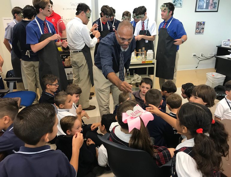 Take a closer look: Columbus High AP Chemistry teacher Ludwig Baez shows first graders from St. Brendan School a test tube used in lab experiments. The young students came to visit the high school next door during a STREAM Day field trip.