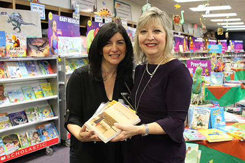 Author Christina Diaz Gonzalez, left, presents copies of all her books to St. Mark School Media Specialist Sandy Garcia, who will prepare them for circulation in the school's library. Diaz Gonzalez was invited to St. Mark March 25 to kick off the school's book fair and discuss her books with students.