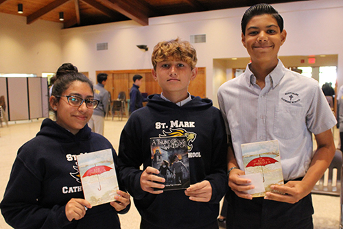 "Historical fiction all around: St. Mark School students hold up their copies of ""The Red Umbrella"" and ""A Thunderous Whisper,"" written by Christina Diaz Gonzalez. From left: Emily Cruz, Connor Cates and Pedro Jimenez."