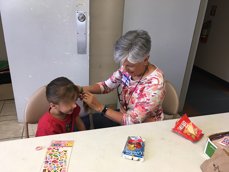 Silvia Muñoz, director of social action for the Jesuits' Pedro Arrupe Institute in Miami, combs the hair of a child who arrived at the Casa Oscar Romero shelter in El Paso, Texas, with her father. Muñoz spent two weeks in March volunteering at the shelter.