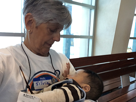Silvia Muñoz, director of social action for the Jesuits' Pedro Arrupe Institute in Miami, holds a child while the mother shows her papers to TSA officials. During her two weeks as a volunteer at an El Paso, Texas, shelter, Muñoz would accompany immigrants to the airport once they obtained the airfare to reunite with family members or sponsors in the U.S.