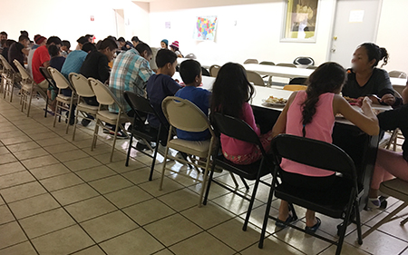 A group of newly arrived immigrants eat a hot meal at the Casa Oscar Romero shelter in El Paso, Texas, after being processed and released by Immigration and Customs Enforcement last March.