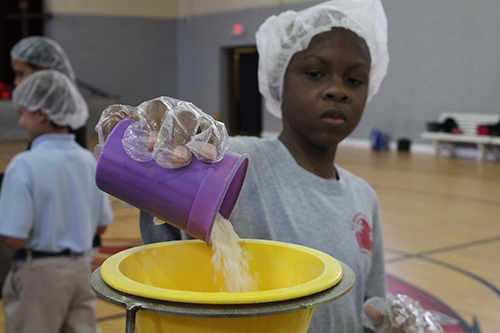 St. Rose of Lima School fourth grader Zakary Phanord pours rice into a funnel during a Meals of Hope packing event in the school gym April 30. During Lent, fourth graders from the school raised more than $ 1,500 to buy and package 6,000 meals, all of which were donated to St. Martha Church, Miami Shores, food pantry.