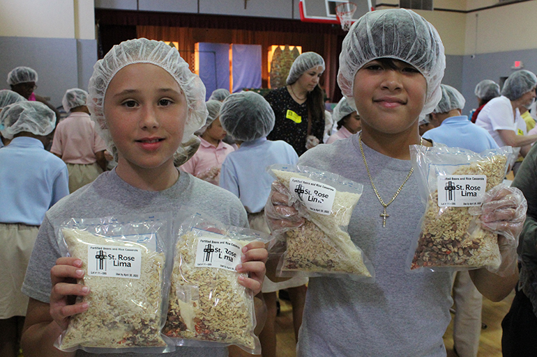 St. Rose of Lima School fourth graders Chloe Humbles and Evan Paul hold up packaged meals at the Meals of Hope packing event in the school gym April 30.
