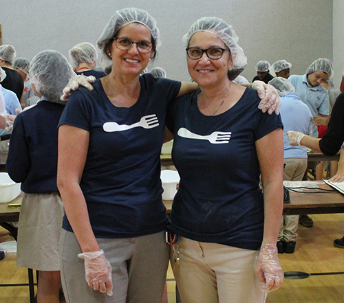 Forks fighting hunger: St. Rose of Lima School fourth grade teachers Paulina Cuadrado, left, and Claudia Karleskey pose for a photo at the Meals of Hope meal packing event at their school April 30.