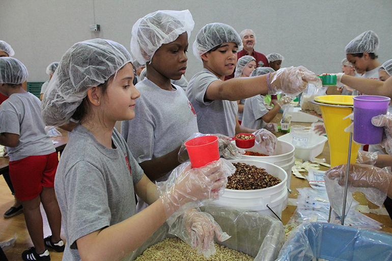 St. Rose of Lima School fourth graders wait to pour in veggie flakes, pinto beans, and soy powder during a Meals of Hope packing event in the school gym April 30.