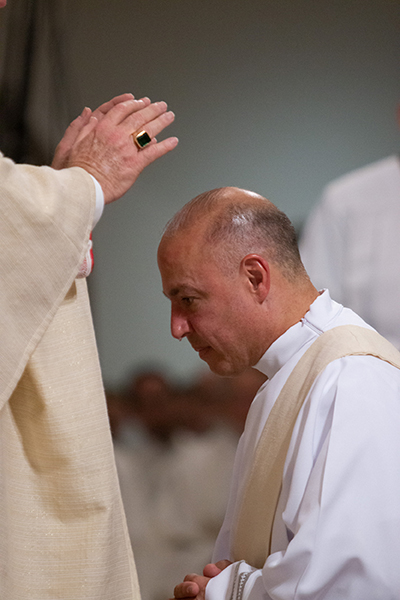 Archbishop Thomas Wenski lays hands on a teary Deacon Elkin Sierra, ordaining him a priest for the Archdiocese of Miami.