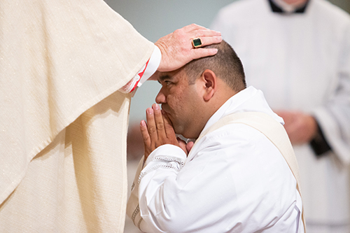 Archbishop Thomas Wenski lays hands on Deacon Martin Muñoz, ordaining him a priest for the Archdiocese of Miami.