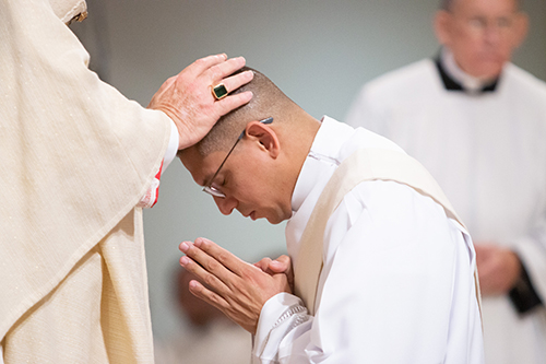 Archbishop Thomas Wenski lays hands on Deacon Yonhatan Londoño, ordaining him a priest for the Archdiocese of Miami.